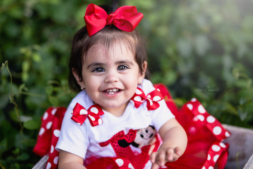Gorgeous little girl with great big hazel eyes smiles at the camera while wearing a Minnie inspired shirt and tutu during her one year milestone session in this portrait by Nature's Reward Photography.