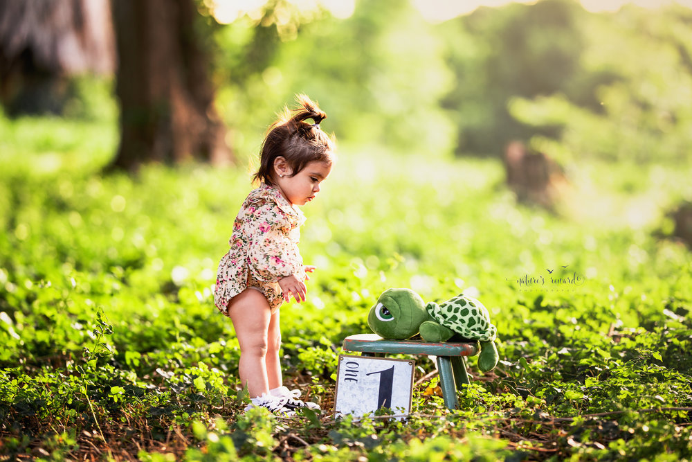 Darling baby girl in a floral romper stands during her one year milestone session looking at her best friend, turtle, in this super cute portrait by Nature's Reward Photography