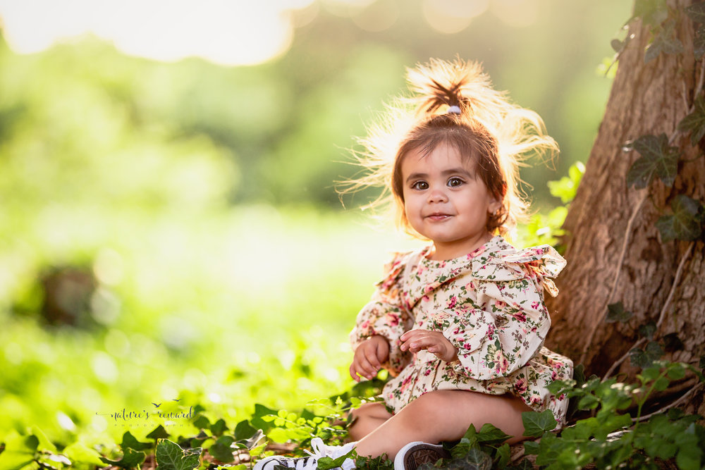 Can this be any cuter?  Darling big eyed baby girl sits in a floral romper next to a tree with ivy on it while sunshine lights up her hair and she smiles.  A portrait by Nature's Reward Photography
