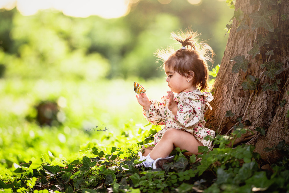 The Bub and the butterfly!  Darling portrait where this little one was checking out her thumb so I added a butterfly overlay created by Obsidian dawn to bring in the magic a bit.  I love the floral romper she is wearing as she sits next to this amazing tree with ivy growing up the sides, in this portrait by Nature's Reward Photography