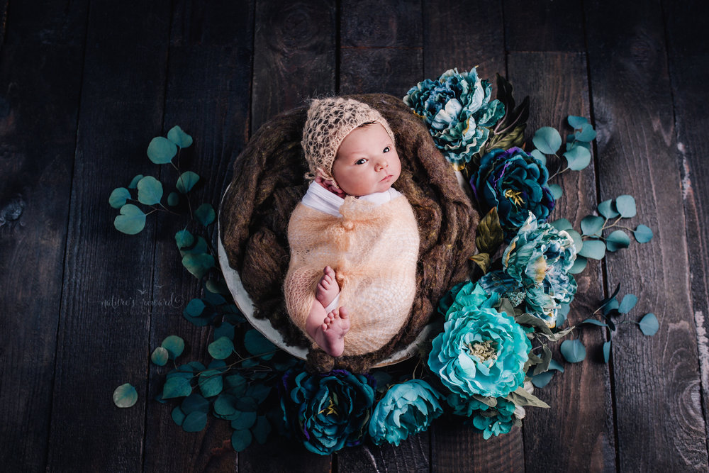 Baby girl swaddled in white and a coral knot wrap wearing a coral knot bonnet by The Crafty European laying in a white wooden bowl of green wool fiber surrounded by teal and blue flowers in this portrait by Nature's Reward Photography