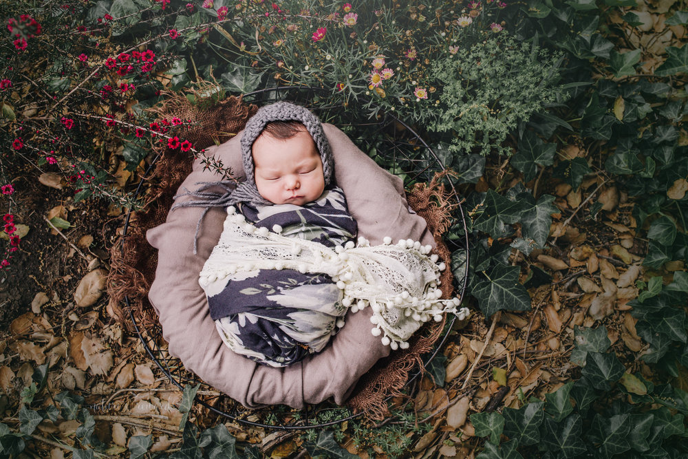 Newborn baby girl in a garden of pretty  flowers and ivy in a bowl of brown textures wearing a grey and white floral wrap and a grey bonnet in this portrait by Nature's Reward Photography