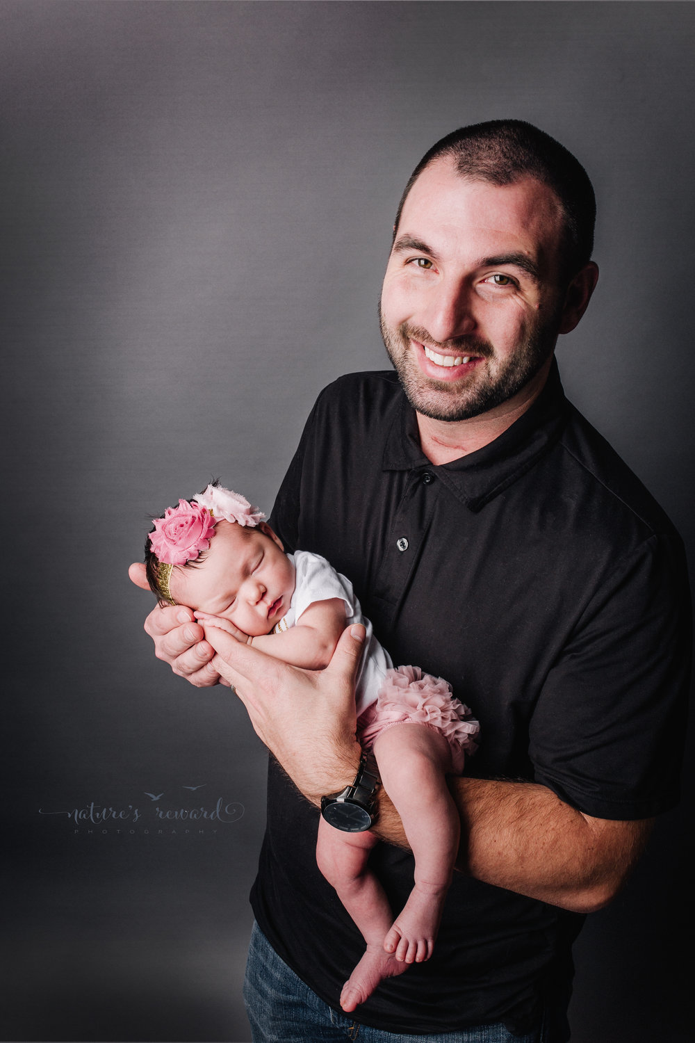 Newborn baby girl in a white onesie and pink ruffle butt pant wearing a floral headband safe in her father's hands in this lovely dad and me Portrait by Nature's Reward Photography