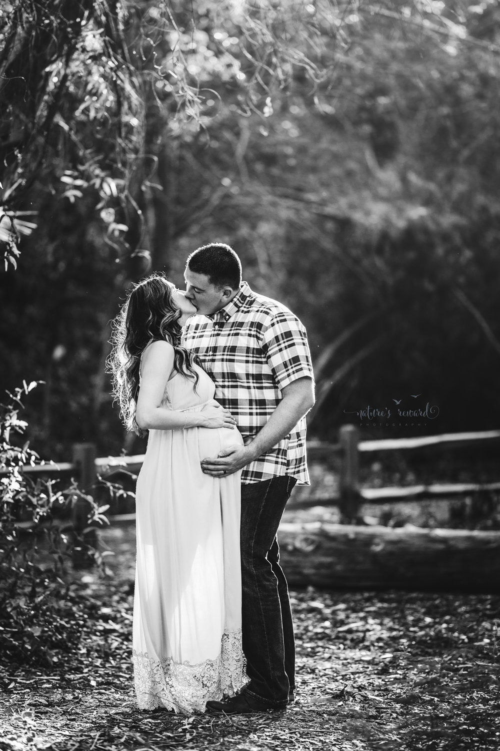 Beautiful expecting mother in a blue maternity gown with her husband in jeans and a blue plaid button down shirt in beautiful light, embrace, in a park setting in this black and white maternity portrait taken by Nature's Reward Photography.