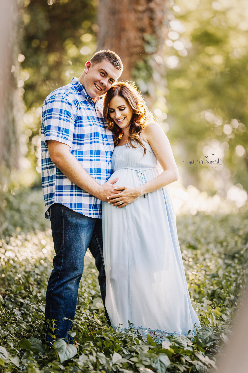 Beautiful expecting mother in a blue maternity gown with her husband in jeans and a blue plaid button down shirt in beautiful light in a park setting in this maternity portrait taken by Nature's Reward Photography.