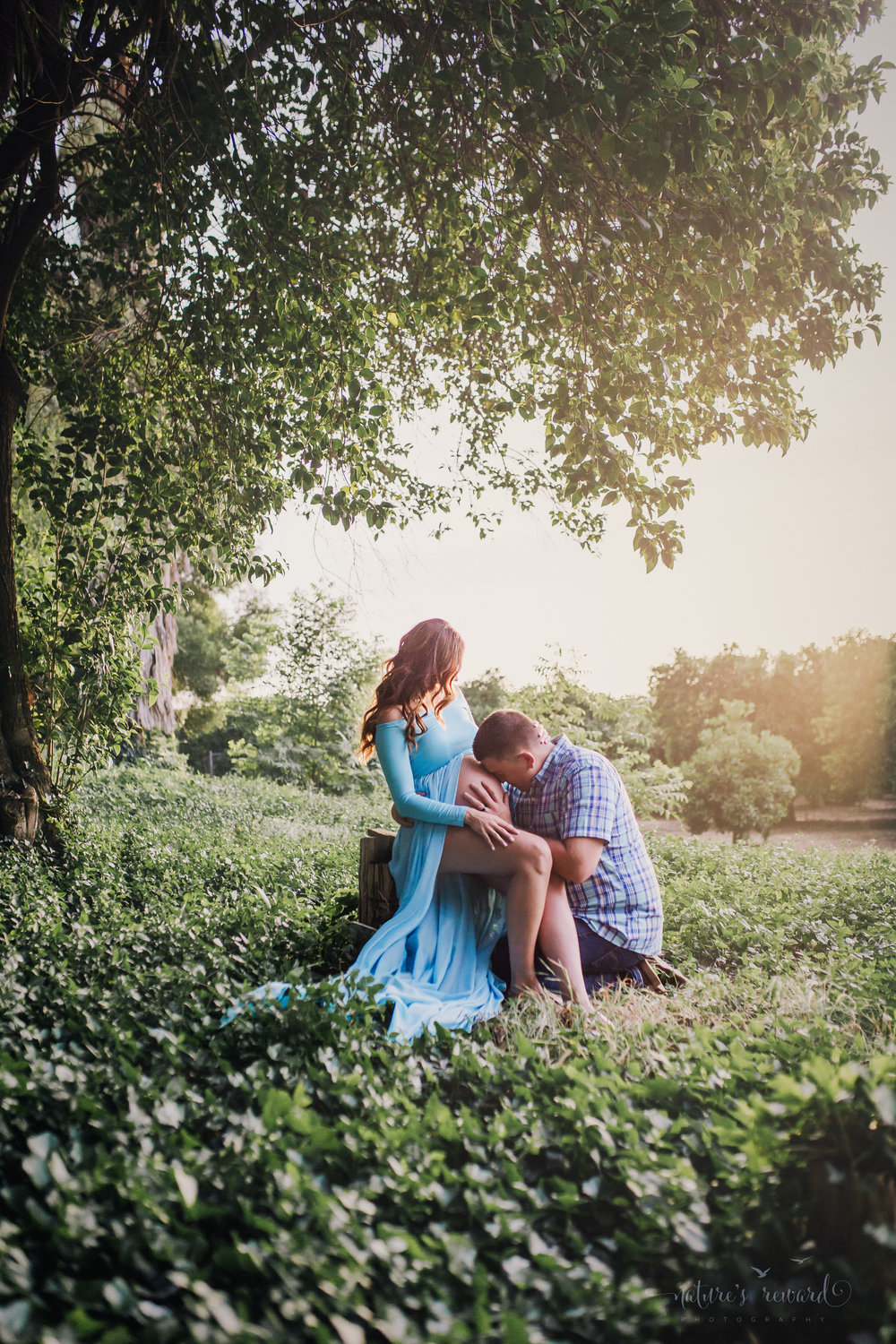 Beautiful expecting mother in a blue maternity gown with her husband in jeans and a blue plaid button down shirt in beautiful light are caught in this candid moment celebrating their miracle in a park setting in this maternity portrait taken by Nature's Reward Photography.