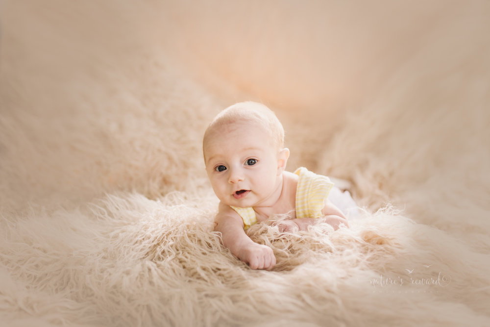 Tummy time portrait of a 3 month old baby girl on a white fluffy blanket in this portrait by Nature's Reward Photography.
