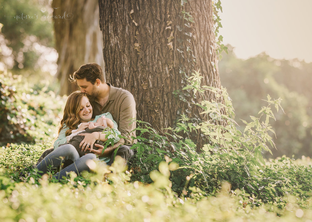 A loving family sits under the shade of a majestic tree while loving on their 3 month old daughter in magical sunset light in this portrait by Nature's Reward Photography.