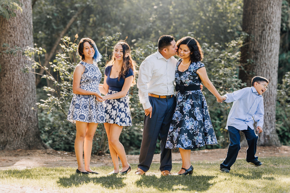 Dad kisses mom and the son runs away! Somebody is jealous!Beautiful family wearing blues and blue florals dresses in this gorgeous family photography portrait by Nature's Reward Photography.