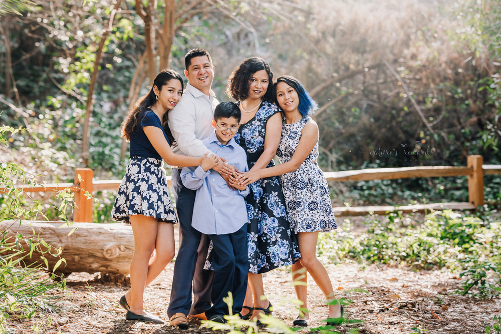 The squish! A hug in the park.Beautiful family wearing blues and blue florals dresses in this gorgeous family photography portrait by Nature's Reward Photography.
