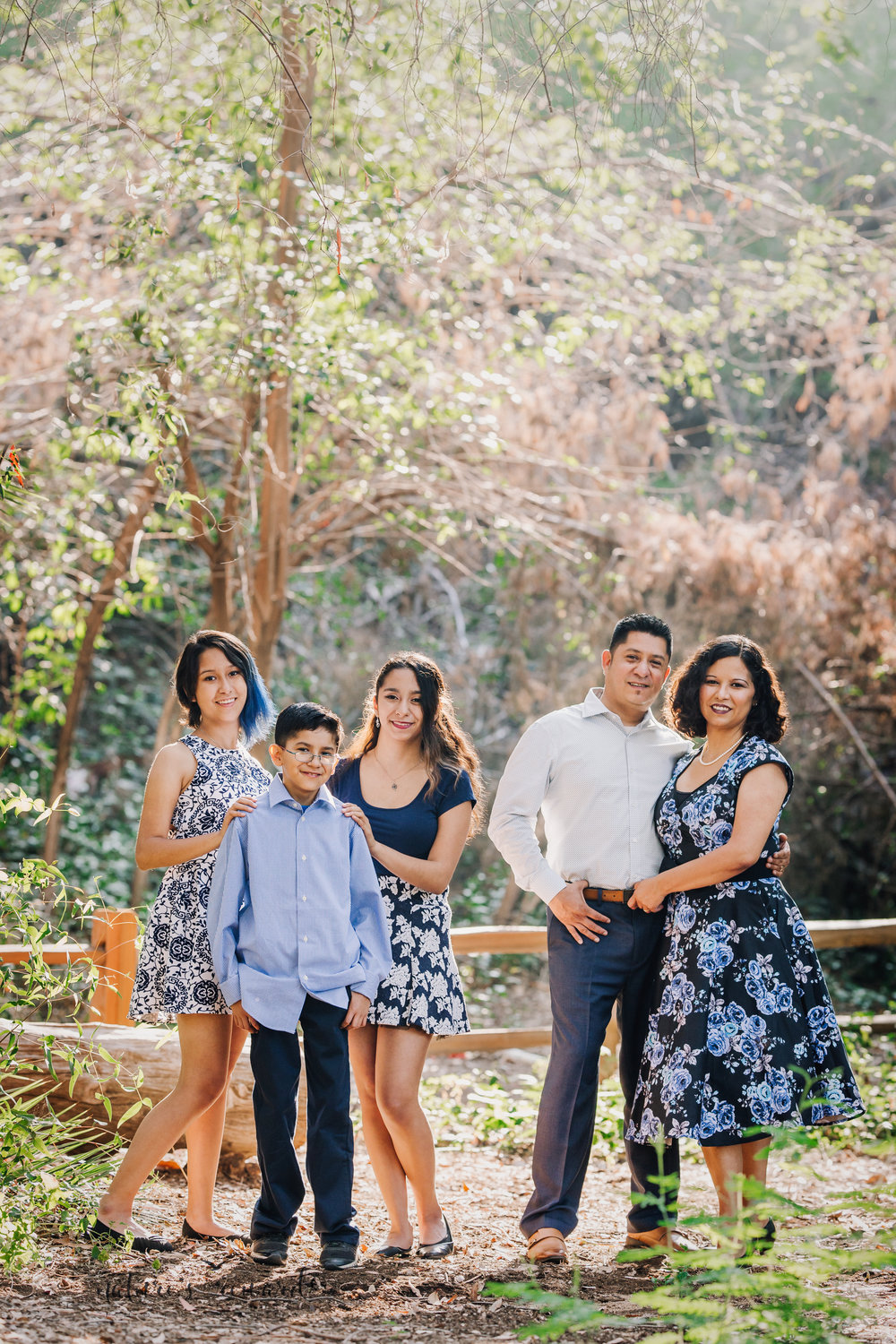 Beautiful family wearing blues and blue florals dresses in this gorgeous family photography portrait by Nature's Reward Photography.