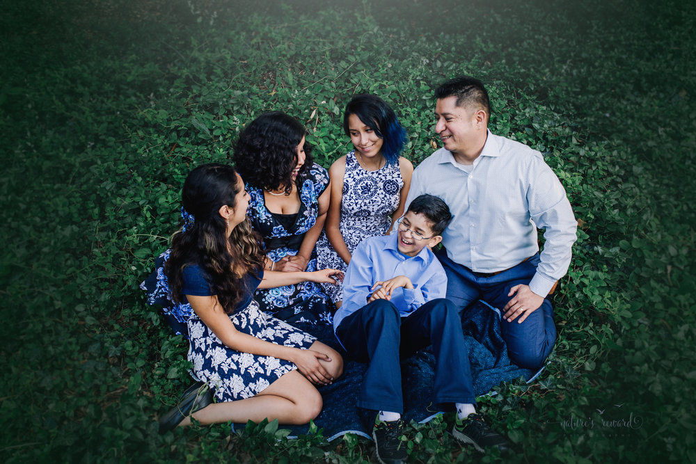 A candid portrait showing how happy this lovely family is wearing blues and blue florals dresses in this gorgeous family photography portrait in ivy by Nature's Reward Photography.