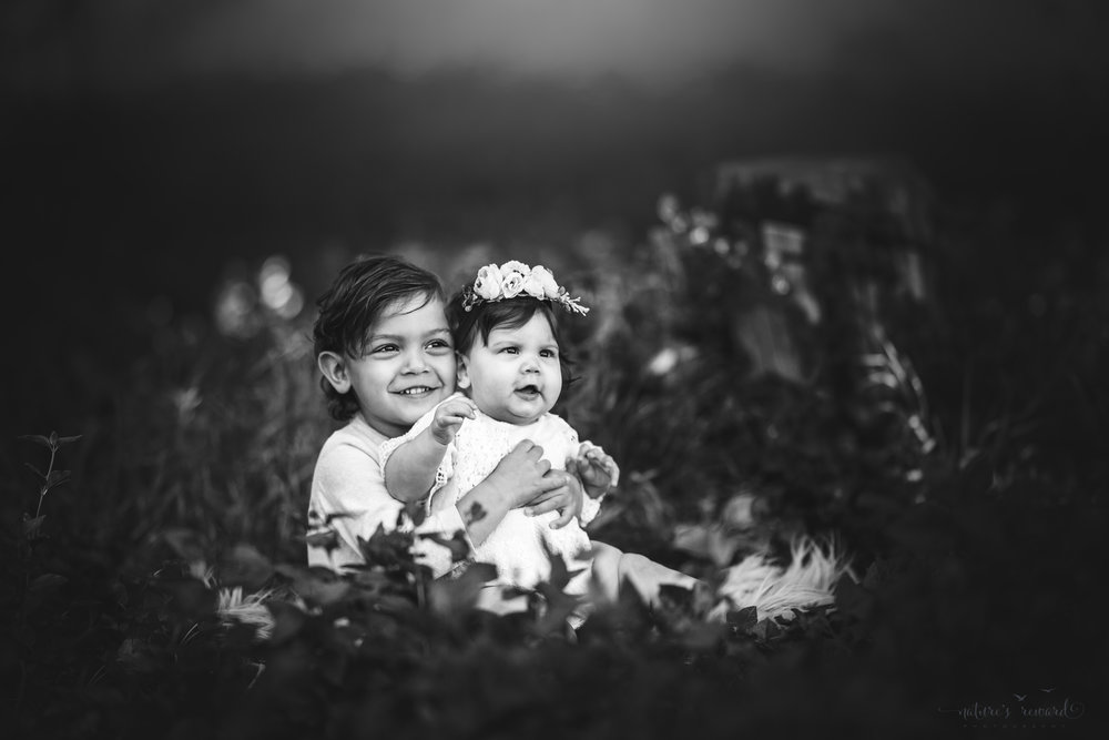 Big Brother holds his little sister in this black and white sibling portrait by Nature's Reward Photography