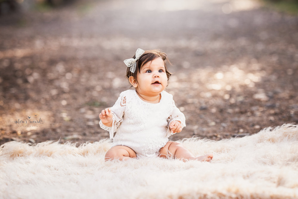 Baby girl sits while wearing a lace romper and flower crown on a tree lined path in this portrait by Nature's Reward Photography