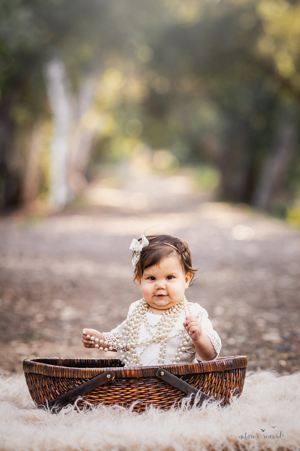 Baby girl sits while wearing a lace romper, pearls, and flower crown on a tree lined path in this portrait by Nature's Reward Photography