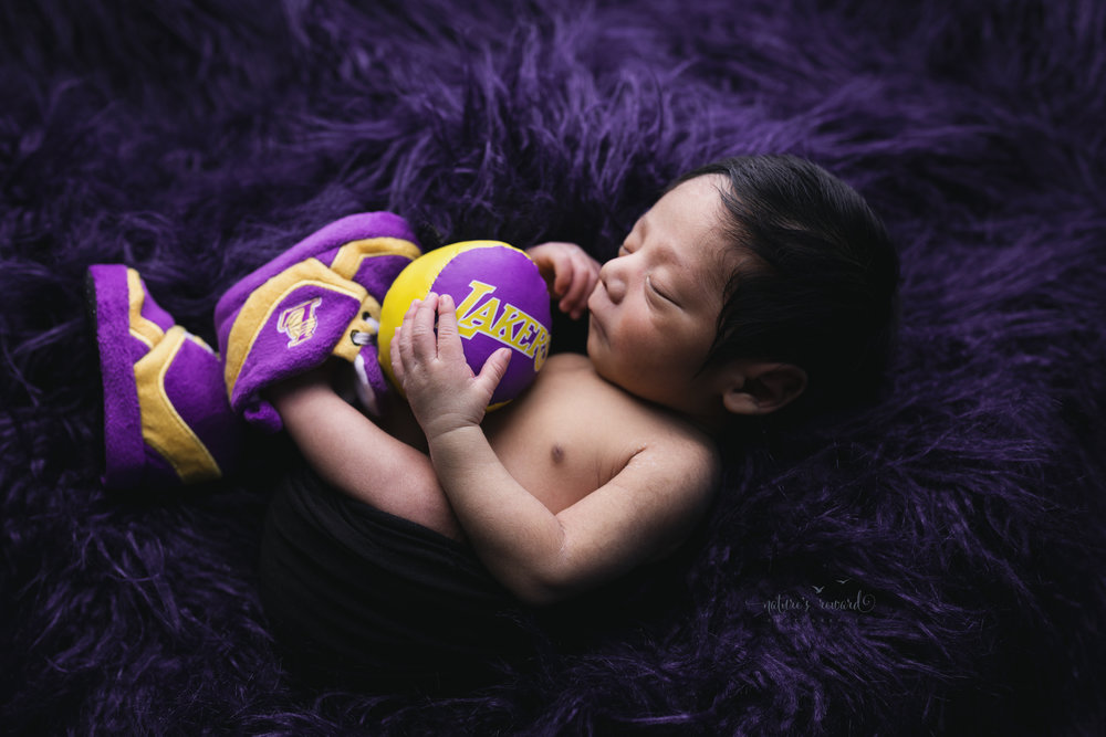 A born laker fan.  Gorgeous Newborn Baby Boy wearing laker's booties holding a baby sized laker's Basketball on a bed of purple faux fur in this newborn portrait by Nature's Reward Photography