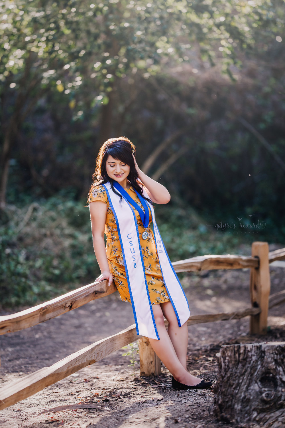 Class of 2018, California State University, San Bernardino Graduate wearing a yellow dress and Medallion, bathed in light, surrounded by the lush green of a park in Redlands, California in this Senior Portrait by Nature's Reward Photography.