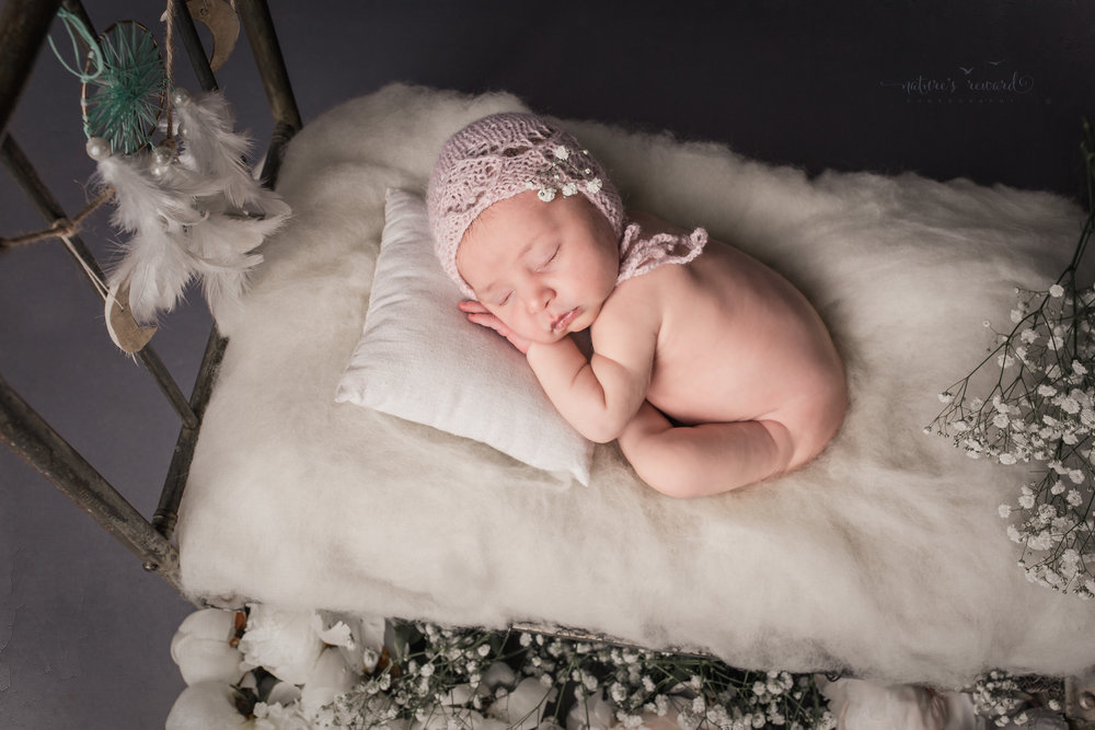 Newborn baby portrait in whites and soft pink, laying on a doll bed. A Portrait By Nature's Reward Photography, a San Bernardino Family, Child, and Newborn Baby Photographer.