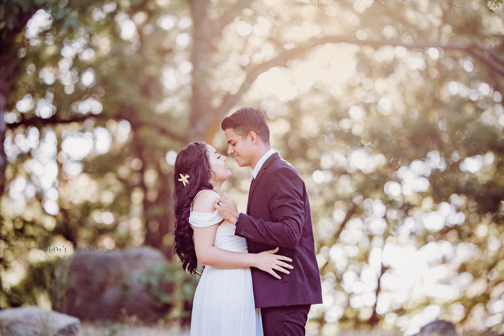 Beautiful bridal session- groom lifts the sleeve of here dress in this flirty portrait By Nature's Reward Photography