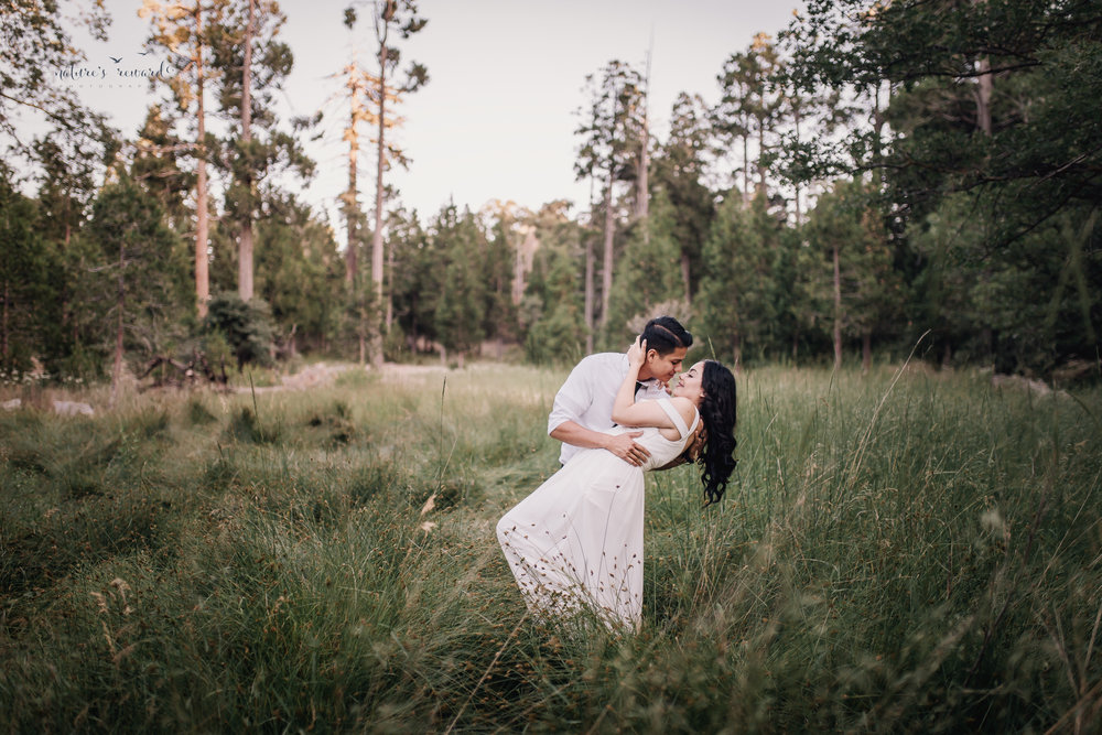 The dip in a field surrounded by trees in this bride and groom portrait by Nature's Reward Photography