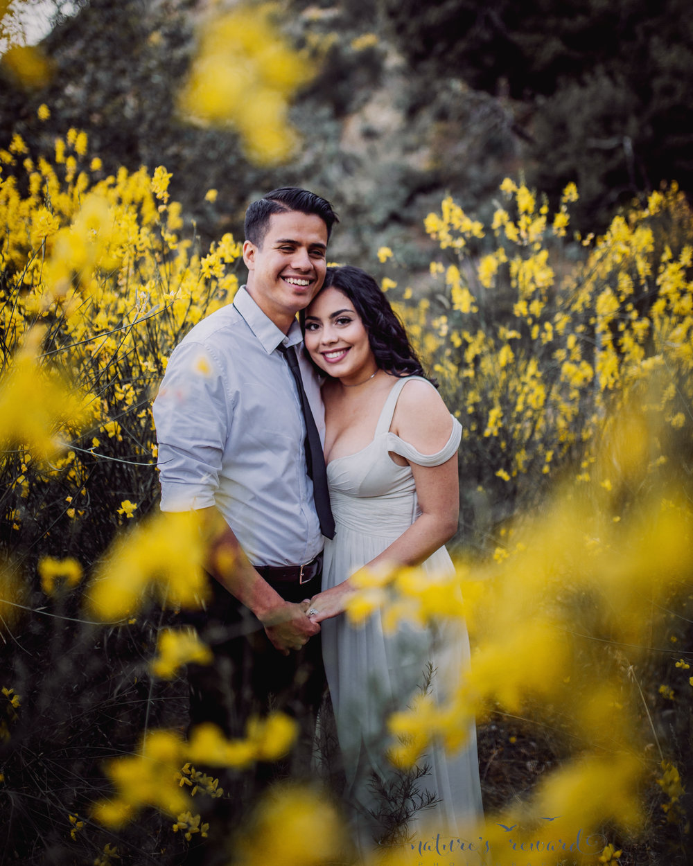 The couple surrounded by wild yellow flowers in this portrait by Nature's Reward Photography