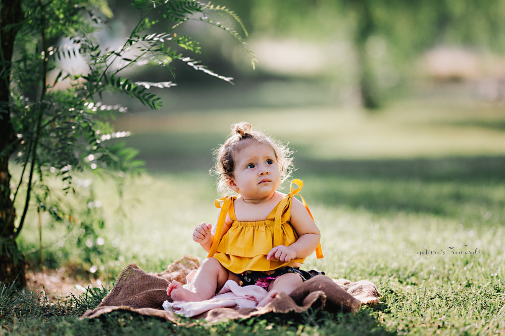 Lovely baby in yellow top during her sitter session portrait session by Nature's Reward Photography