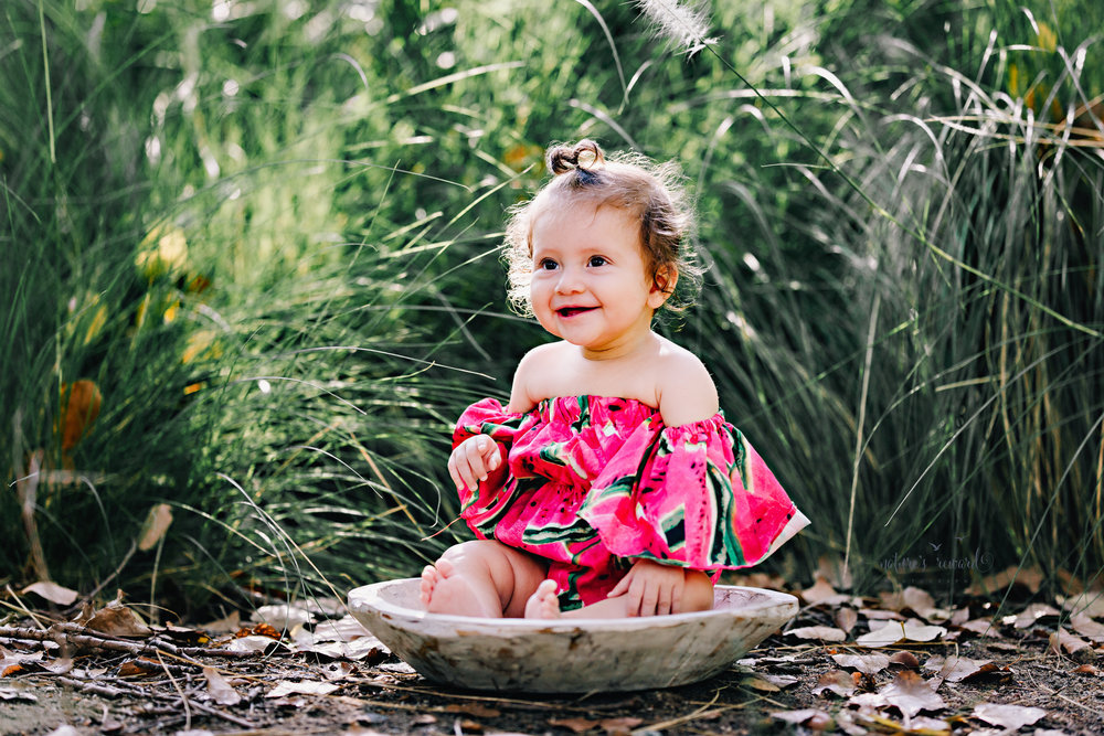 Gorgeous Baby girl in a watermelon off the shoulder romper sitting in front of the long reeds of grass during her sitter session in this portrait session by Nature's Reward Photography