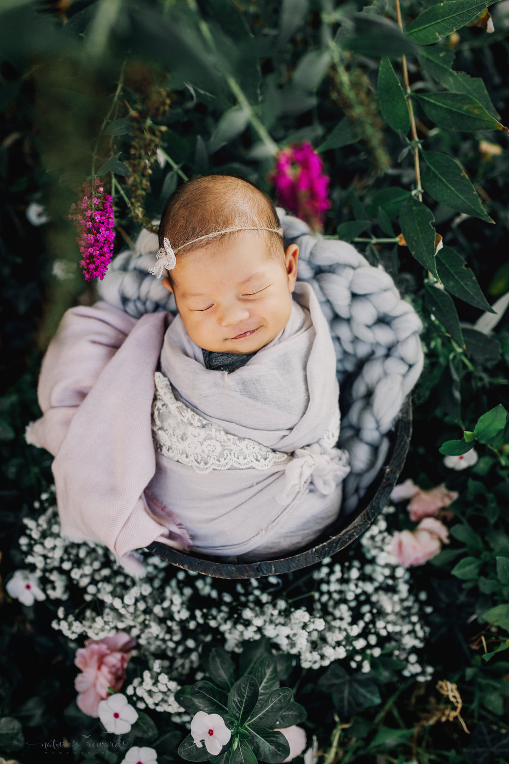 Gorgeous baby Newborn Girl in a bucket swaddled in  a neutral wrap with pink and grey basket stuffers in a bucket in a garden surrounded by lush greens and white flowers, purple flowers, and pink carnations and my favorite baby breath in this portrait by Nature's Reward Photography.