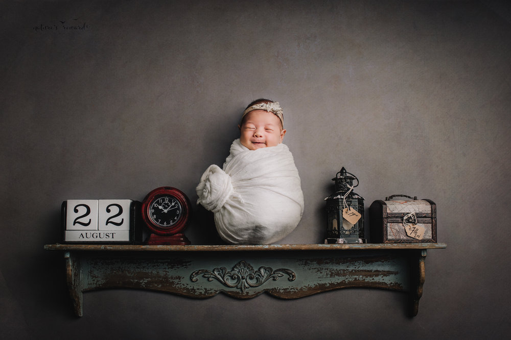 Sweet baby girl on a shelf with the best grin ever and her birth story in this portrait by Nature's Reward Photography