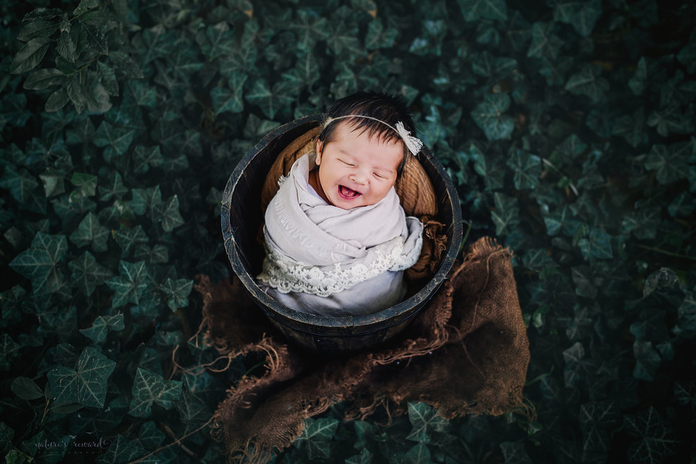 This sweet newborn baby girl in subtle neutral lace adorned wrap in a brown bucket in a bed of ivy smiling. A portrait by Nature's Reward Photography