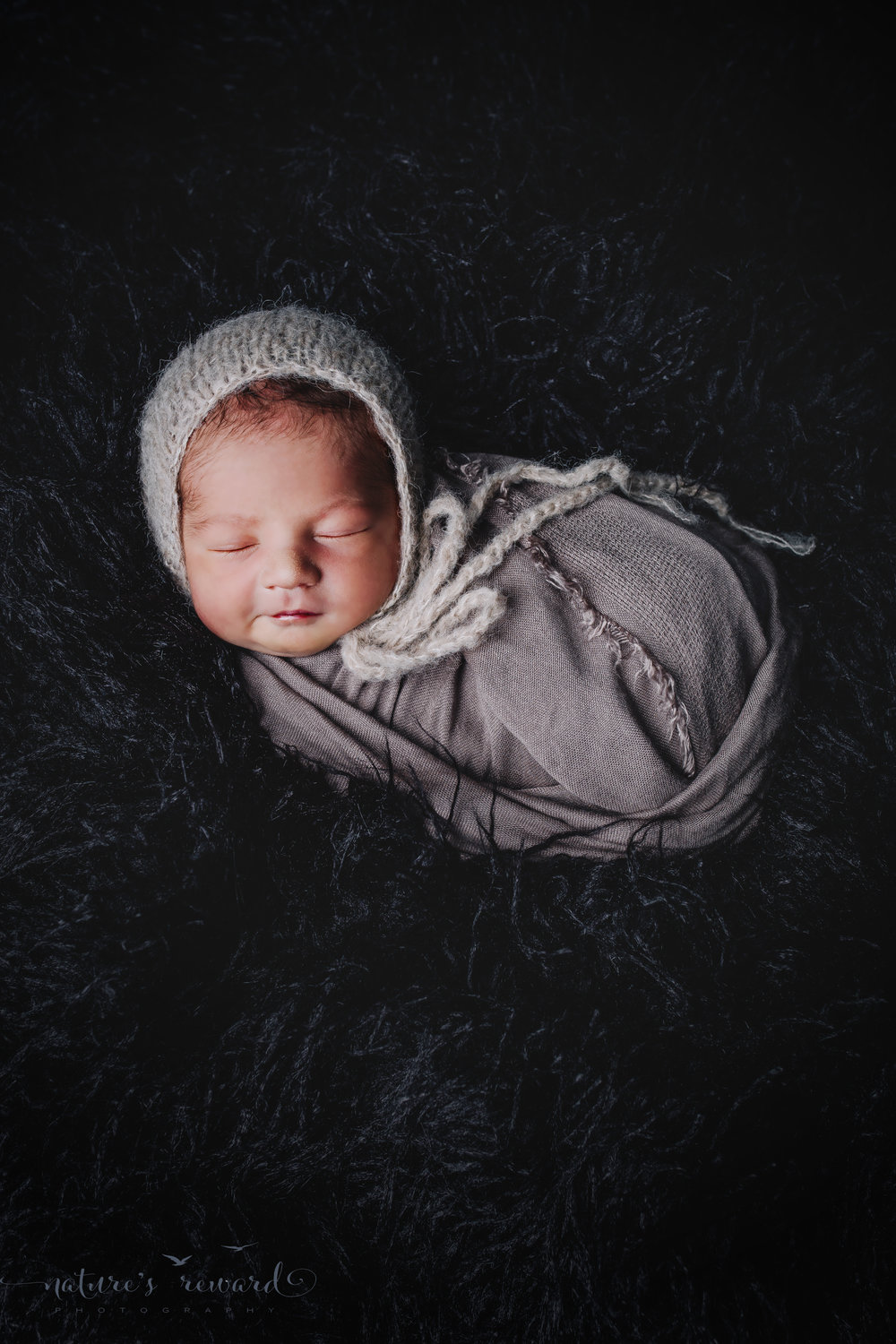 Beautifully swaddled and wearing a neutral bonnet on a bed of black furs, this gorgeous portrait of a newborn baby boy by Nature's Reward Photography