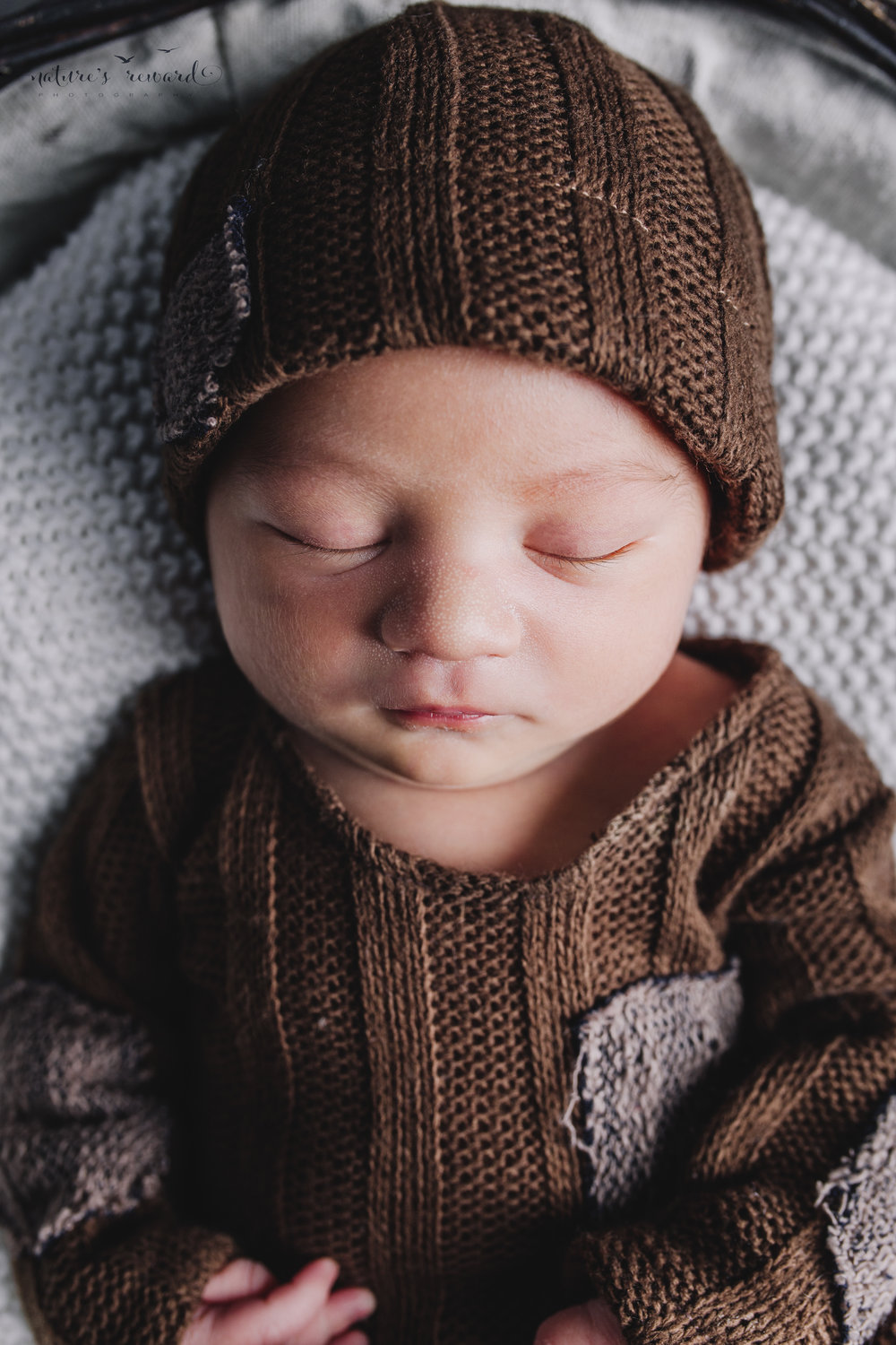 Newborn baby boy portrait wearing a brown outfit and matching cap by Nature's Reward Photography