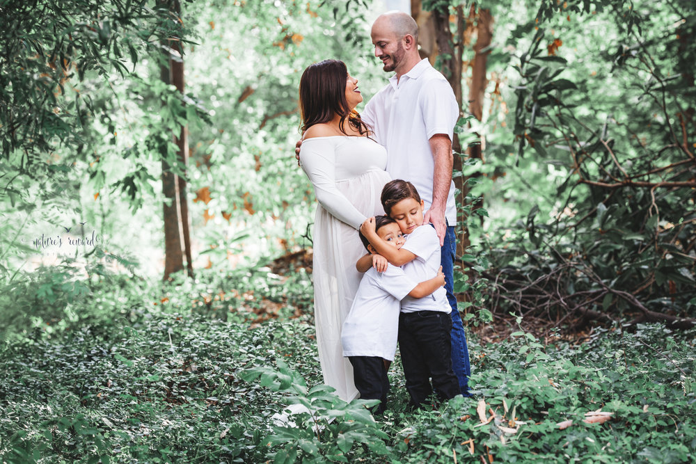 Gorgeous family in whites in a lush green park celebrate the upcoming arrival of their new family member in this lovely maternity session portrait by Nature's Reward Photography
