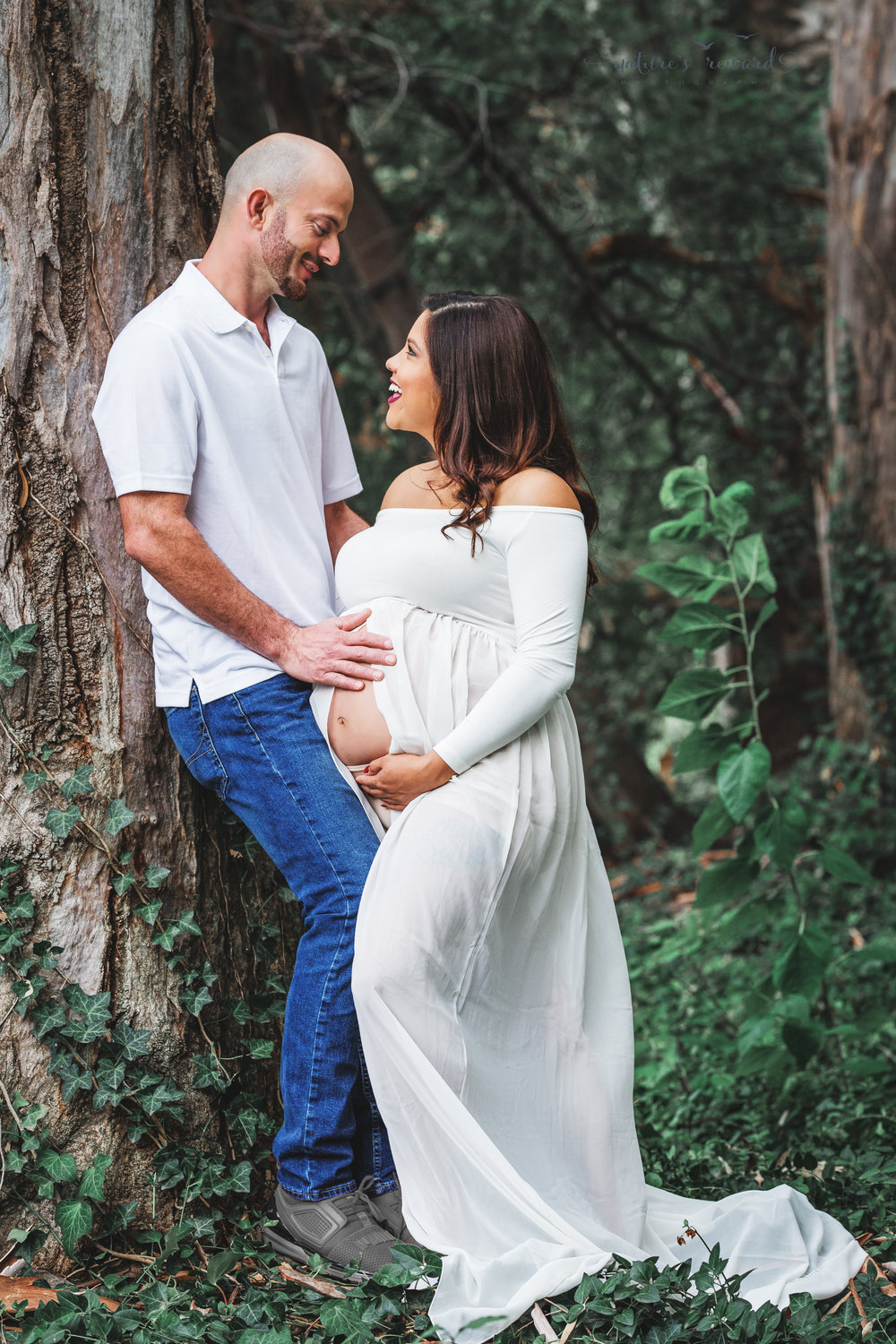 Beautiful couple celebrating the upcoming birth of their 3rd son in this maternity session portrait in white by Nature's Reward Photography.