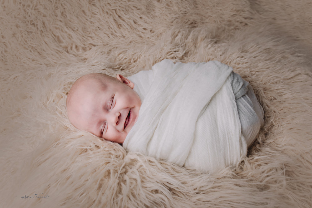 Two month old baby boy newborn baby boy session in whites smiling- a portrait by Nature's Reward Photography