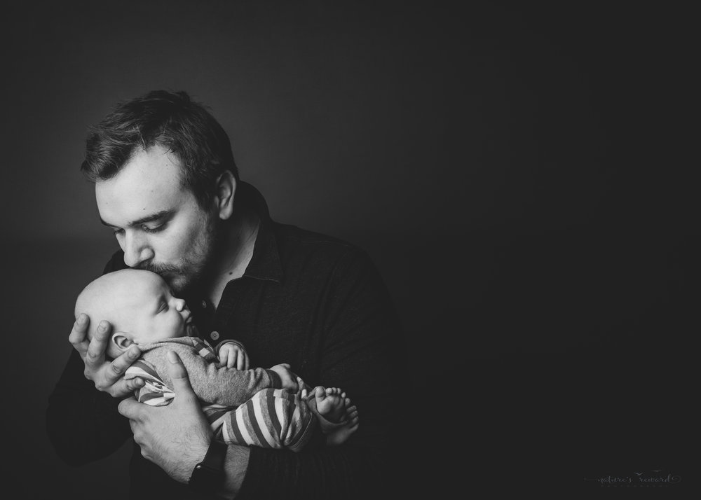 Black and white portrait of2 month old newborn baby boy being held by his loving father- a portrait by nature's Reward Photography