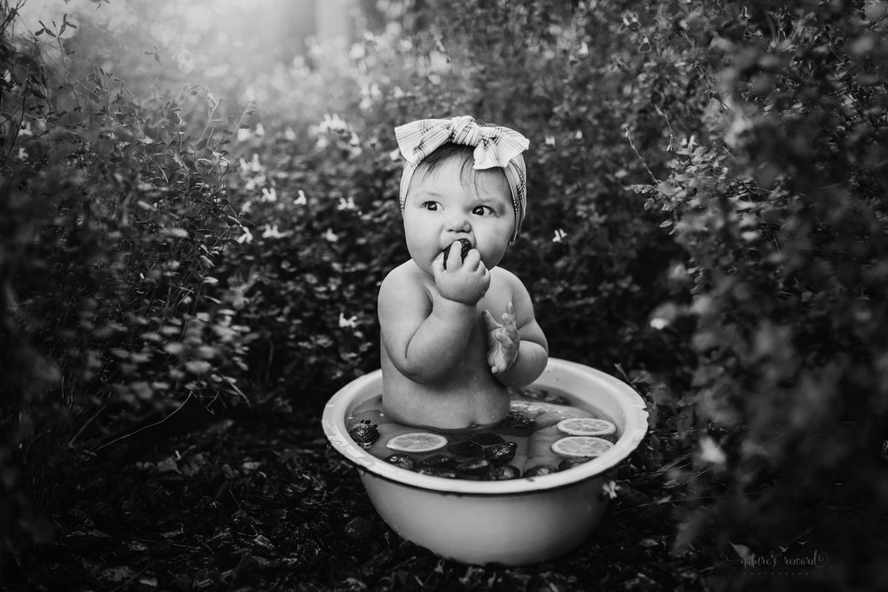 Black and white portrait of a 6 month old little girl during her sitter session taking a fruit bath of strawberries and lemons in garden of kissy lips flowers- a portrait by Nature's Reward Photography