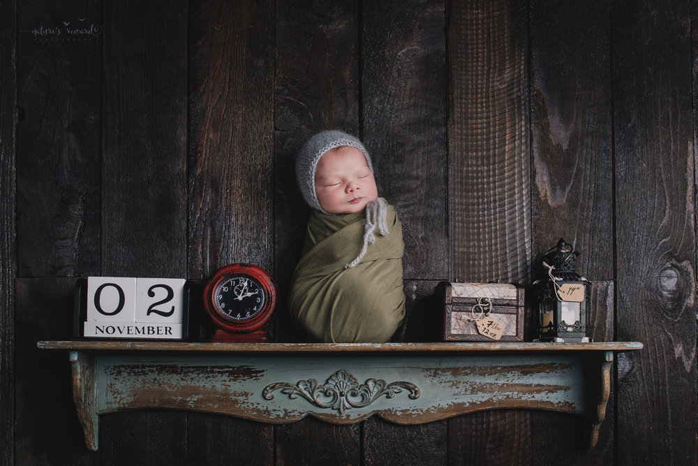 The birth story portrait- A baby on shelf with his date, time, weight, and length- a portrait by Nature's Reward Photography