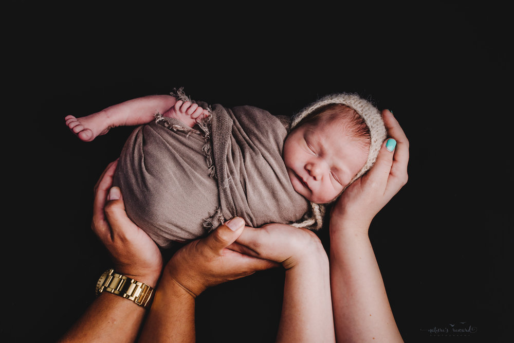 Swaddled and wearing a bonnet being held by his mother's and father's hands -a portrait by Nature's Reward Photography