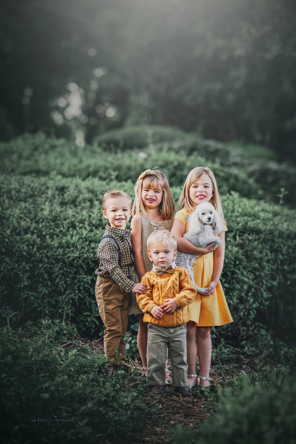 Beautiful sibling portrait in yellows and tan in a green lush park setting with their furry  little brother- A portrait By Nature's Reward Photography!
