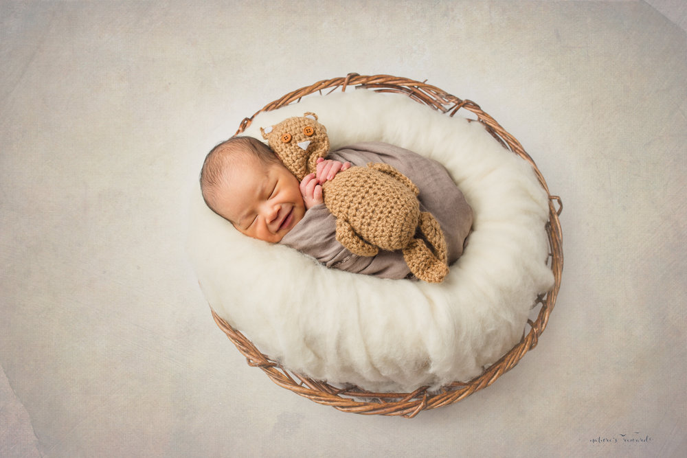 A newborn baby boy in tans and whites, laying a in bowl smiling a portrait by Nature's Reward Photography