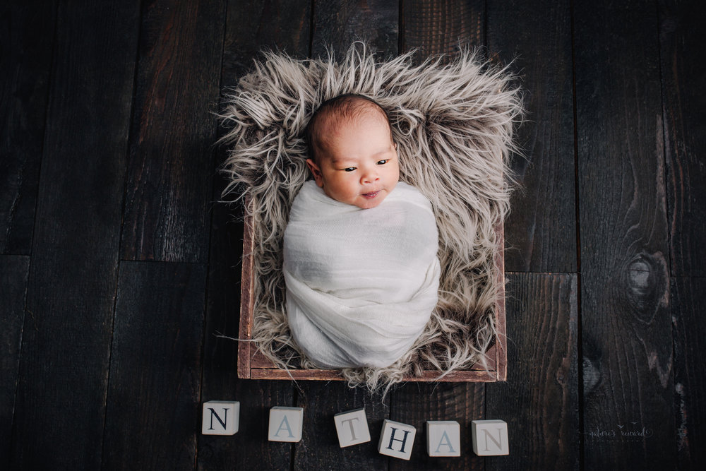 A newborn baby boy swaddled in white on a dark wood floor with blocks spelling his name a portrait by Nature's Reward Photography
