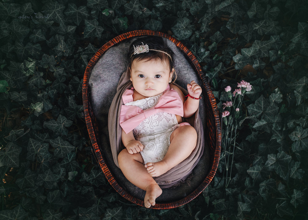 Lovely 10 week old newborn baby girl sin a darling white and pink outfit, in a bed of ivy- a portrait by Nature's Reward Photography