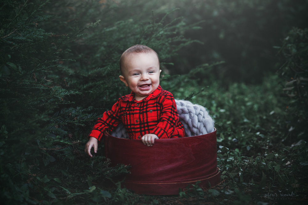 6 Month sitter baby boy in red inside a red circular box in a lush green park setting in Redlands, Ca. by San Bernardino photographer- Nature's Reward Photography