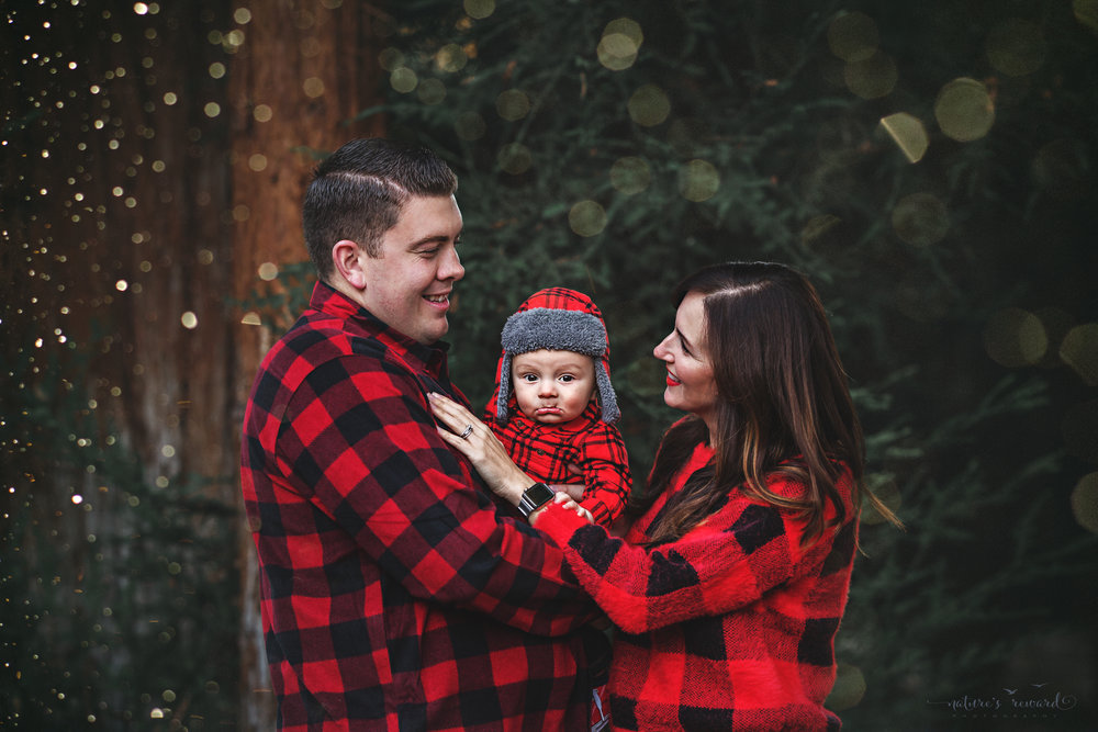 "Titled- ""I Saw Mommy Kissing Santa Claus"" 6 month old baby boy with his mommy and daddy in a lush green park setting in Redlands, Ca. by San Bernardino photographer- Nature's Reward Photography"