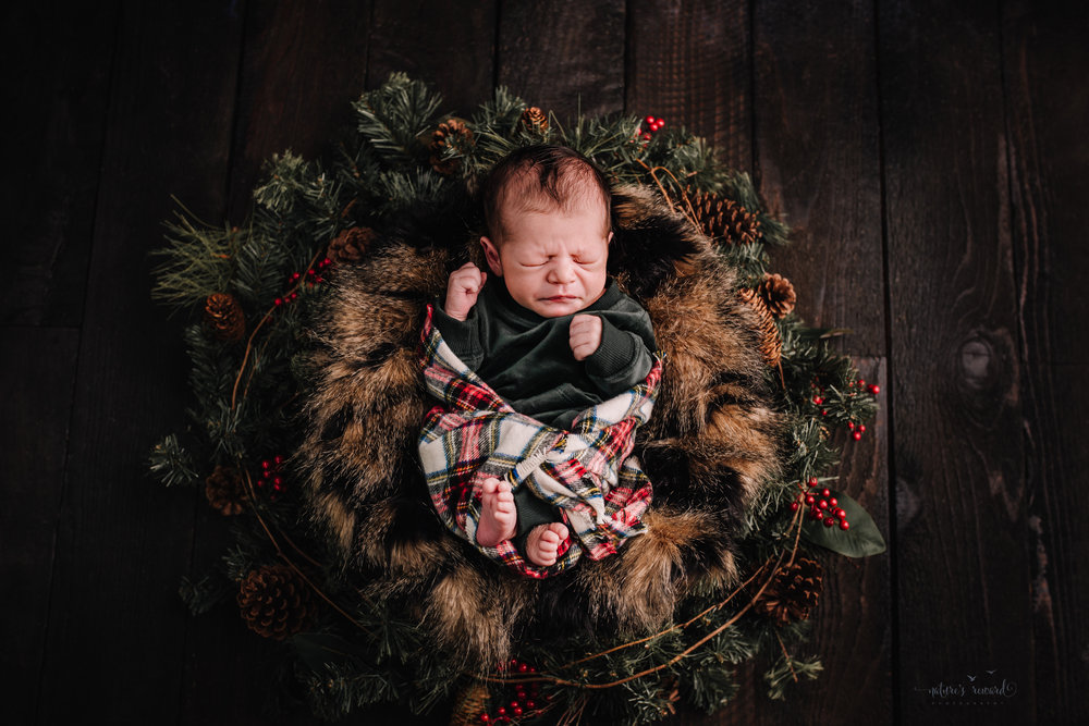 Newborn baby boy sin a green nighty and flannel blanket on a bed of furs in a Christmas wreath on a dark wood floor by san Bernardino's maternity, newborn and family photography, Nature's Reward Photography