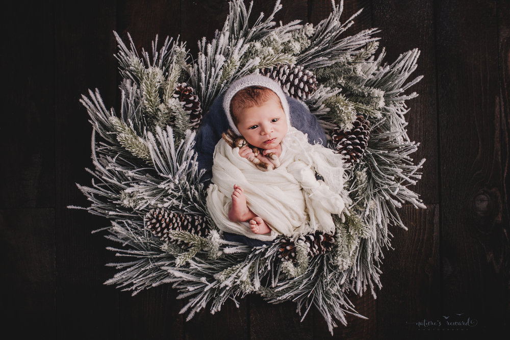 Newborn baby boy swaddled in white in winter wreath on a dark wood floor by san Bernardino's maternity, newborn and family photography, Nature's Reward Photography