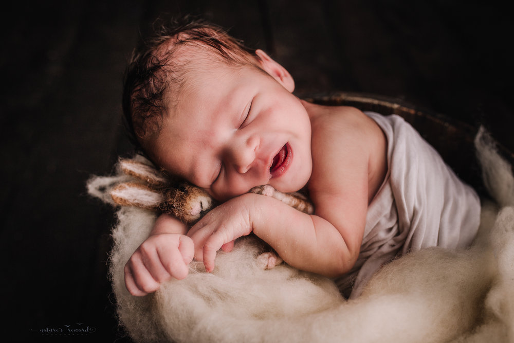 Newborn baby boy swaddled in white in bucket of white fluff on a dark wood floor by san Bernardino's maternity, newborn and family photography, Nature's Reward Photography