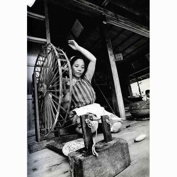 Weaver twisting basha threads from plantain fiber on spinning wheel Okinawa Japan 1960