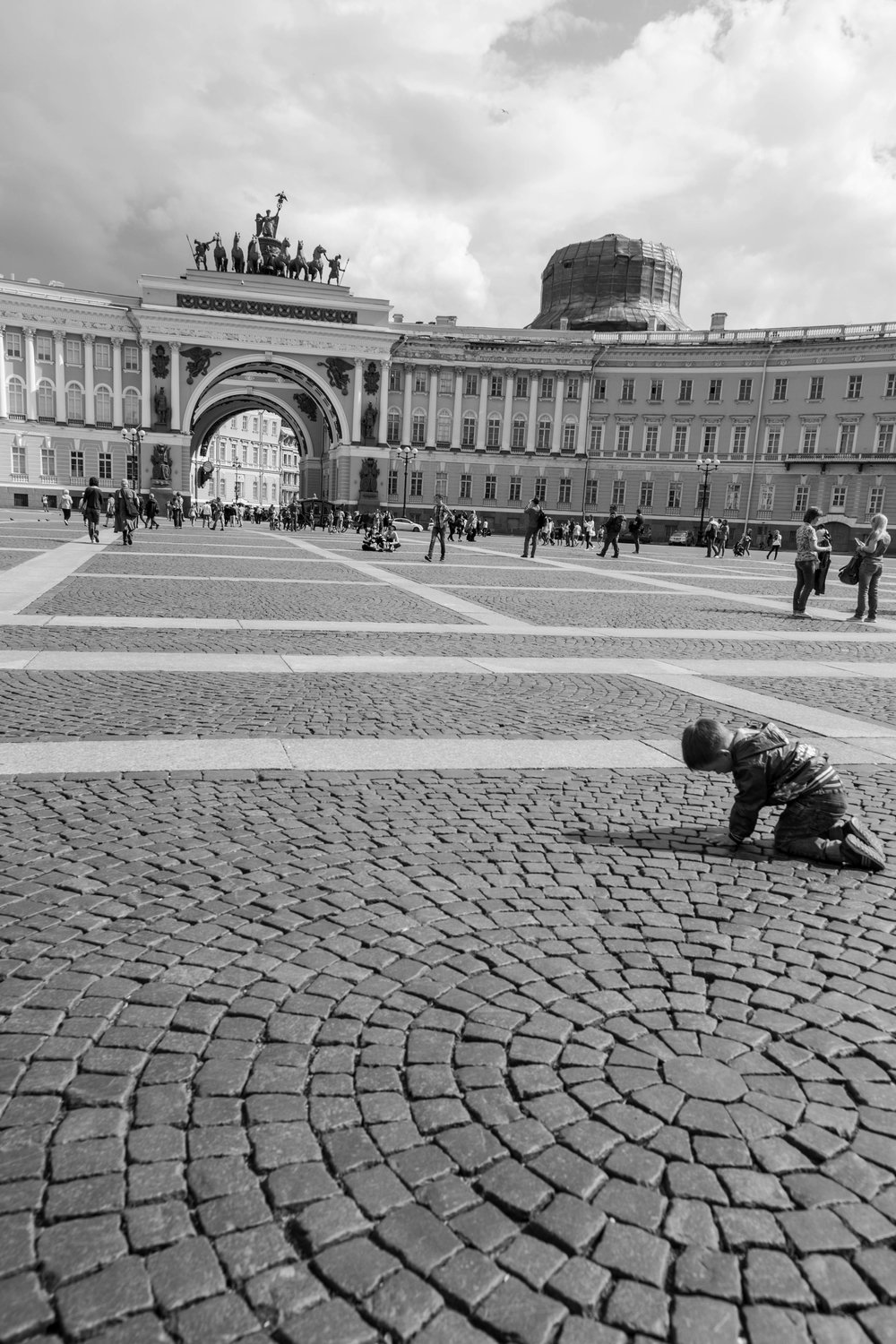 A child entertains himself in Palace Square.